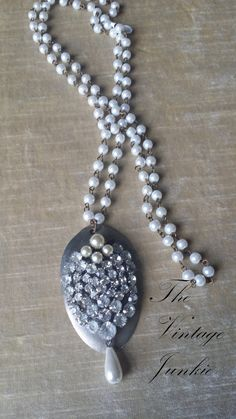 This is a long, gorgeous, Victorian inspired spoon necklace. The chain made from soft white, glass pearls. The pendant is made from an upcycled, silver plated spoon with a vintage, rhinestone brooch embellishment.  This piece is overall @21.5 long with the ability to be worn short (Simply loop the pendant end through the looped end of chain around you neck like you would a scarf).