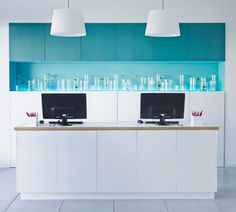 Wall cabinets with grey-turquoise doors and base cabinets with white doors