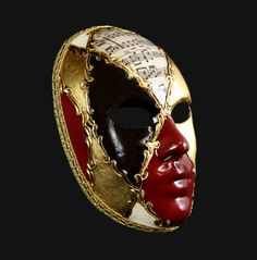 A graphic decoration with the classical Venetian signs: gold, red, the diamonds of Harlequin dress and music paper...whit a total black look this mask is perfect.