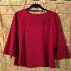 Red Blouse with 3/4 sleeves A beautiful red blouse. Has a boxy cut that fits nicely and is very flattering. There are six buttons going down the back of the blouse. You can leave them all buttoned or. Unbutton the bottom two or three to make it a bit more revealing. Tops Blouses