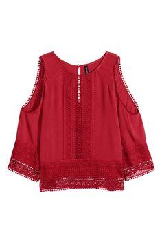 24 Blusa con hombros abiertos: Blusa en viscosa arrugada con encaje calado ancho. Mangas tres cuartos con hombros abiertos y cierre de lágrima con botón en la nuca.