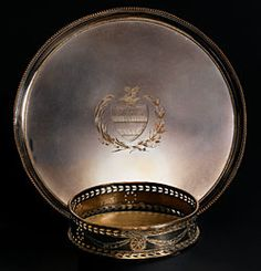 "Interested in owning fashionable goods, Washington wrote to Lafayette on October 1783 requesting that he send him an array of silver-plated tea wares and other tablewares including ""Two smaller size [salvers] for 6 wine glasses each"" and ""eight bottle sliders."" By March 1784 Washington had received the items from France, including this salver (tray) and bottle slider (wine coaster). The tray is decorated with a simple beaded edge and engraved coat of arms"
