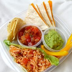 This Mexican-inspired bento is filled with cheese quesadilla wedges, Spanish rice, guacamole, salsa, tortilla chips and yellow pepper strips. A dry lettuce leaf helps to keep the rice separate from other foods and small containers with lids house the salsa and guacamole.