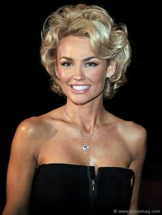 Kelly Carlson with a short curly hairdo.