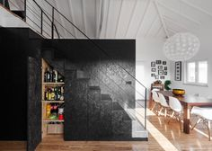A black box built from oriented strand board houses the kitchen and bathrooms of this converted barn home in Portugal, and also integrates a staircase leading to the mezzanine floor above.