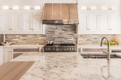 A wood and quartzite island top is finished with a stainless steel sink and polished nickel faucet is fixed facing a stainless steel oven range positioned between walnut stained drawer fronts adorning polished nickel pulls and a gray and white quartzite countertop.