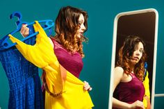 Fashion and shopping. Woman preparing to party trying dress choosing clothing. Attractive young woman shopper looking in mirror standing in clothes store.