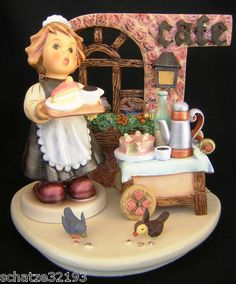 """This is the Hummelscape """"Strudel Haus"""" featuring the darling little """"Maid to Order"""" Figurine, created by Hummel to commemorate the """"Off to Work"""" Series Figurines. This sweet little Hummel figurine is a waitress about to serve a cup of coffee and a slice of cake just cut from the luscious looking cake sitting on her serving cart in her Cafe. She would make a wonderful maitre d' in a Restaurant, but likes her little sidewalk Cafe with pastries and pies sitting on the windowsill."""