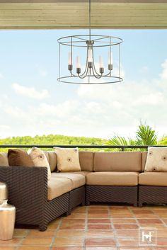 """The Portico Drum Outdoor Living Pendant delivers a modern twist on the classic drum shade with its """"there, not there"""" design. The upswept arms hold five candelabra bulbs surrounded by opal or seeded glass tubes. Available in your choice of Coastal Outdoor Finish."""
