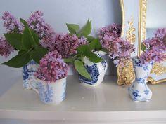 Sweet lilac sprigs in vintage blue vases on mantel