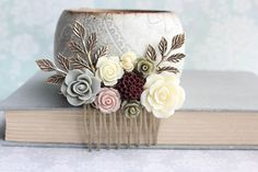 A beautiful romantic flower collage hair comb in deep wine red, ivory cream, khaki green, sage green and dusty rose. The resin flower are set on an antique brass gold filigree hair comb with sprigs of antique gold brass leafy branches. This would be a beautiful wedding hair accessory or would make a romantic accessory for holiday parties, beach vacations or just because. This is floral comb will add a touch of romance to any day! Floral Collage Measurements (including branches) Width = 3.2…