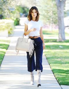 Alessandra Ambrosio wears a white shirt, tan belt, Henri Bendel Rivington Fringe Tote, Topshopculottes, and Stuart Weitzman The Highland Boots