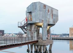 Local residents worked with Berlin-based studio Raumlabor to build the Gothenburg Public Sauna. A wooden bridge projects out in to a harbour to link the sauna on stilts, which is clad in sheets of rusty corrugated metal. Scandinavian Saunas, Building A Sauna, Green Building, Sunken Hot Tub, Gothenburg Sweden, Lebbeus Woods, Public Bathrooms, In Plan, Brutalist