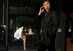 A woman naps at a coffee shop as a man walks past in downtown Seoul, on April 24, 2013. (AP Photo/Kin Cheung)