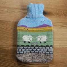Knitted hot water bottle cover with countryside design: including bottle