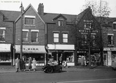 Manchester Road shops (does anyone know the make of car). 1958. Chorlton-cum-Hardy.