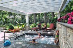 An in-ground spa features therapy jets and an automatic cover, which may be retracted incrementally to allow the water weir to function decoratively. Stone piers support painted wooden pergola supports, unifying stone and carpentry.