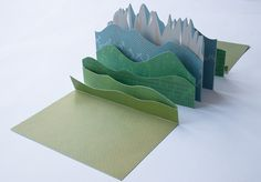"Val di Funes / Villnöss  This silkscreen-printed accordion book features a repositionable Alpine landscape, based on a particular valley in Northern Italy. Viewers are invited to interact with the pages and create their own South Tyrolean landscape.    Serigraph on Stonehenge paper, 8 colors on two sides each, hinged with Hanga paper    2011  6 1/2"" x 9"" x 3/8""  Edition of 8"