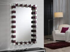 Mirror with central mirror plate. Frame formed by prisms of beveled mirrors, combined with mirrors of amethyst colour. Black wooden support. Ready to hang in horizontal or vertical position.