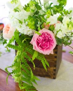 Wooden planters are filled with ranunculus, lisianthus, freesia, irises, stock, wax flowers, and pink and coral garden roses for a touch of color.