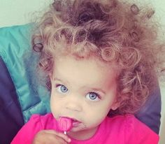 Sweet baby girl with big blue eyes and wild cute hair