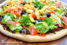 1 Pizza Crust  1 Lb Ground Chuck  1 Package Taco Seasoning  1 Can Ranch Style Beans  Lettuce  Black Olives  Diced Tomatoes  Fritos  Shredded Mexican Style Cheese  Fat Free Catalina Dressing