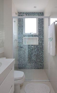 Para dar um toque de cor ao banheiro com bancada e piso brancos, o escritório Rocha Andrade Arquitetura aplicou um mix de pastilhas (Portobello - www.portobello.com.br) em uma das paredes do box
