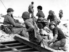 A first wave beach battalion lays low under the fire of Nazi guns on the beach on D-Day, June 6, 1944. One invader operates a walkie talkie radio directing other landing craft to the safest spots for unloading their parties of fighting men.