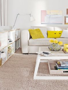 Low white shelves. Pyramidal white coffee table, yellow and white couch. <3