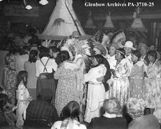 """Dance on the Blackfoot (Siksika) reserve, southern Alberta. Date: [ca. 1935-1945]. Photographer/Illustrator: Gully, F., Calgary, Alberta  Performing the """"Indian Waltz"""". The tipi in the centre of the hall says """"S. Big Snake"""" on the side."""
