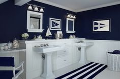 White and navy nautical kids' room features upper walls panted navy blue and lower walls clad in tongue and groove framing white framed mirrors with shelves illuminated by triple white glass bell jar sconces over pedestal sinks leaning against built-in cabinets alongside white and navy striped bathmat for two.