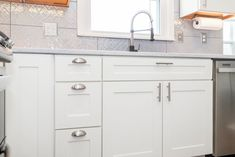 White shaker cabinetry with brushed nickel hardware. Gray backslash tile completes this south Overland Park kitchen.