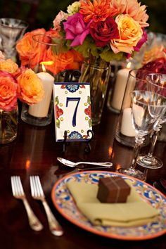 table number with ceramic address number tiles, centerpiece: vibrant flowers in tall, moderately-narrow cylinder vase