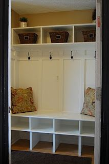 White wood hallway, lots of coathooks, plenty of storage cubbies, bench to sit on to put on shoes