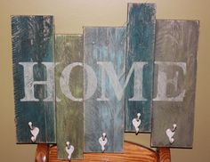 This is a rustic HOME sign painted in blues and green with cream colored hooks for hanging hats, coats or towels. It is 22.5 in wide x 20 in