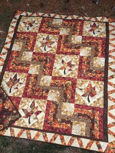 "68"" x 80"" Easy pieced blocks are nestled among maple leaves. A little appliqué and some template piecing are used to create this beauty. Sample uses Hoffman of California 'Maple Lane' line."