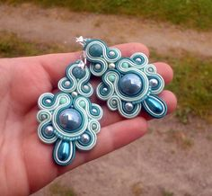 Beautiful, spectacular earrings color sea green, and mint was hand-made laborious technique soutache embroidery. In the center of earrings is a ceramic cabochon green pearl color.  The top ball...