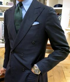 Navy double-breasted jacket, light blue shirt, green tie