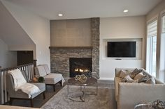 Staged to sell by Stage Right - Lethbridge, the living room in the Empire Homes show home features a beautiful offset fireplace. The designers kept the room neutral and comfortable.