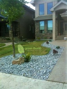 Rustic crushed rock bed with cobblestone edging and a small accent boulder. The edging provides a clean edge that eliminates the need for trimming.