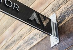 incorporating black finishes and polished metals in the lower, public level signage and warm wood tones in the upper, residential floor signage