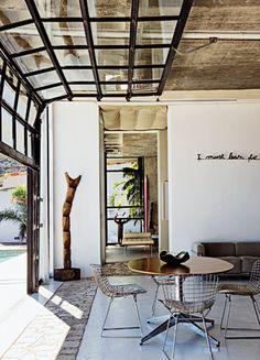 """<p style=""""text-align: left;"""">L'immense baie vitrée se rétracte grâce à un système électrique. Installés sur les chaises Bertoia achetées au..."""