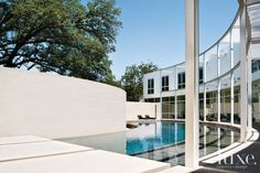 This pool mimics the unusual curved design of the elegant glass, limestone, stucco and steel house was inspired by a 100-year-old Oak Tree growing in the middle of its 2-acre lot in Dallas' Preston Hollow neighborhood.