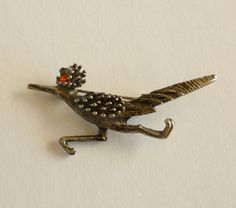 Beautiful vintage road runner bird brooch. This road runner pin is made of textured silver tone metal. The feathers on his body and head have a raised relief and a red rhinestone for an eye.Measurements:5.5 cm  (2.17 inch)  x  2.5 cm  (1 inch)Condition:  Excellent