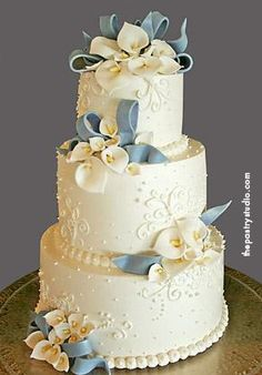 Mary Wedding Cake - This southern cake features sugar-paste cala lilies and delphinium blue bows for a wonderful reception held at lpga international.