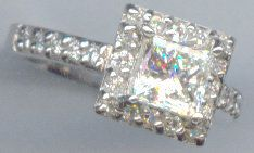 This ring is a 14 kt. white gold custom ring design with a computer aided design. It has .39 carat, prong set round diamnds. The center diamond is a 1.01 carat princess cut, I color, VS2 clarity.   www.facebook.com/middiajewelry  middia53@gmail.com