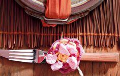 Em um almoço ou jantar, cada detalhe da mesa faz diferença e impressiona os convidados. Aqui, os talheres ganham um aspecto delicado, presos a uma flor de crochê
