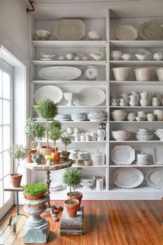"Sinauer displays her collection of old French mugs, iron stone pitchers, and iron stone plates on open shelving. ""Just to have everything laid out in front of you has been wonderful and we really use everything on a daily basis,"" she says."
