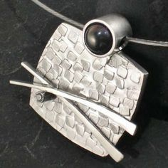 Stunning, unique pendants created using a variety of metalworking techniques. Some incorporate precious stones and precious metals in Oriental flavored designs.