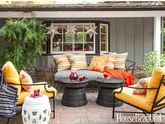 On the patio, the slate-blue tones of Restoration Hardware's Carmel daybed, Pottery Barn's Frog Rain drum side tables, and Brown Jordan's Venetian chairs echo the house's siding.